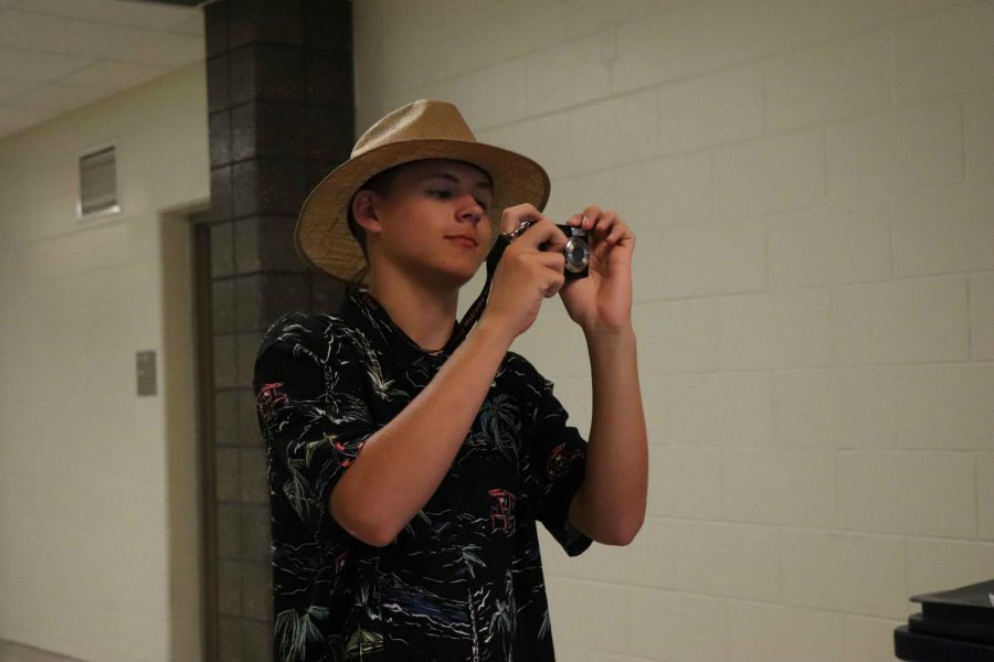 As he snaps a picture in the hall, junior Jack Kennedy shows off his school spirit.  During homecoming week on Tuesday, Sept. 18, the spirit theme was tacky tourist.