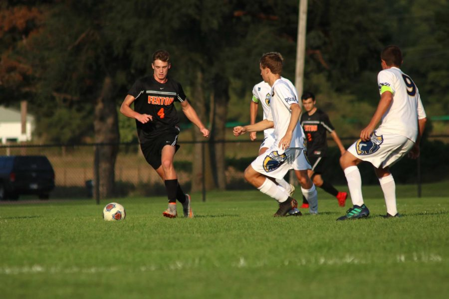 Racing to the goal, senior Brady Young dodges his Owosso opponents. The boys varsity soccer team won their game against Owosso with a score of 6-0 on Sept. 12.