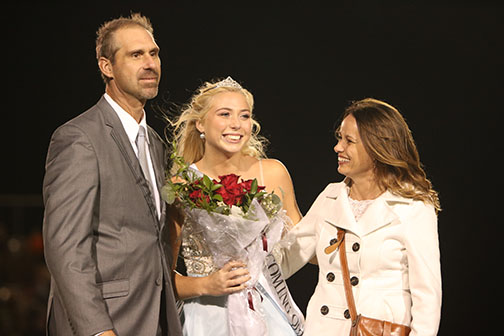 Standing with her parents, senior Chloe Idoni smiles at the crowd. Idoni was crowned the 2018 homecoming queen.