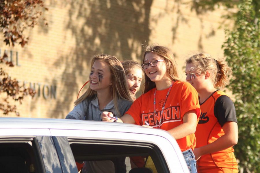 With her fellow golf teammate, freshman Kierstan Lapa smiles while riding through the homecoming parade. Those who were in the parade tossed candy onto the ground for parade viewers.