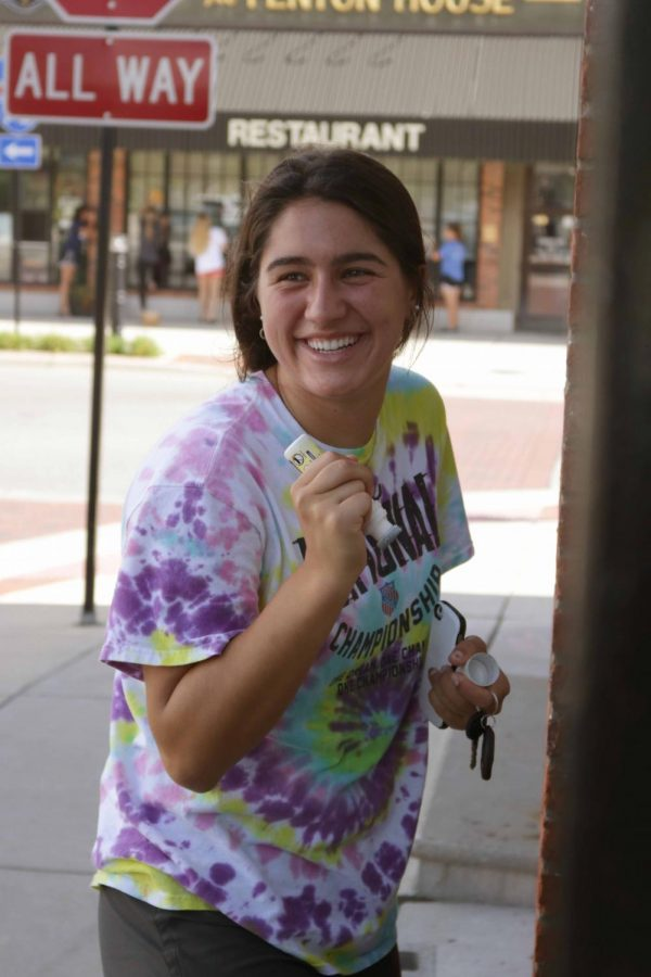 Holding a paint brush, senior Delaney Miesch laughs while painting the windows of downtown businesses in Fenton for Homecoming week.  Members of Student Council painted Fenton-related messages on businesses such as Fenton House.