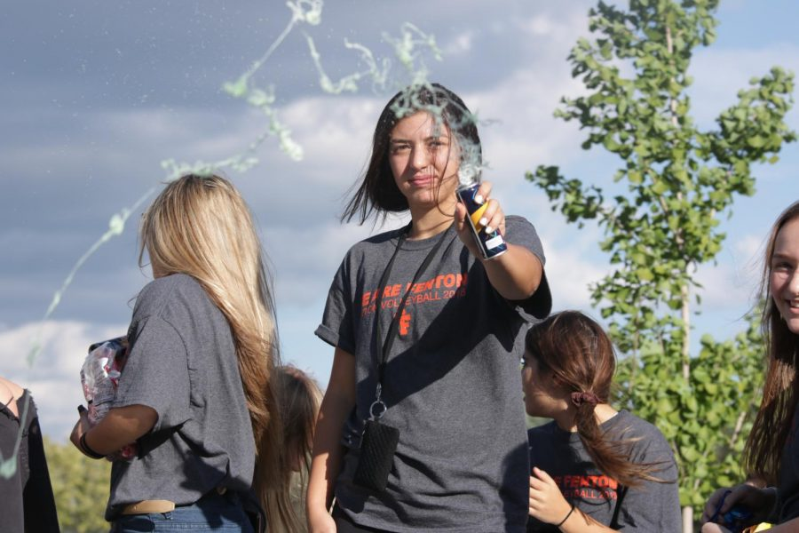 Moving through the homecoming parade, junior Jessica Bright sprays spectators with silly-string.  The homecoming parade was on Sept. 21