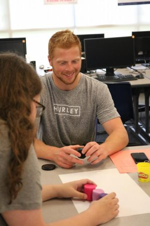 Smiling during the first day of school activity, senior Spencer Gabler talks to his group about what design they are planning to do. Gabler played with Play-Doh as they made a pretty flower landscape with his 4 other members in his group.