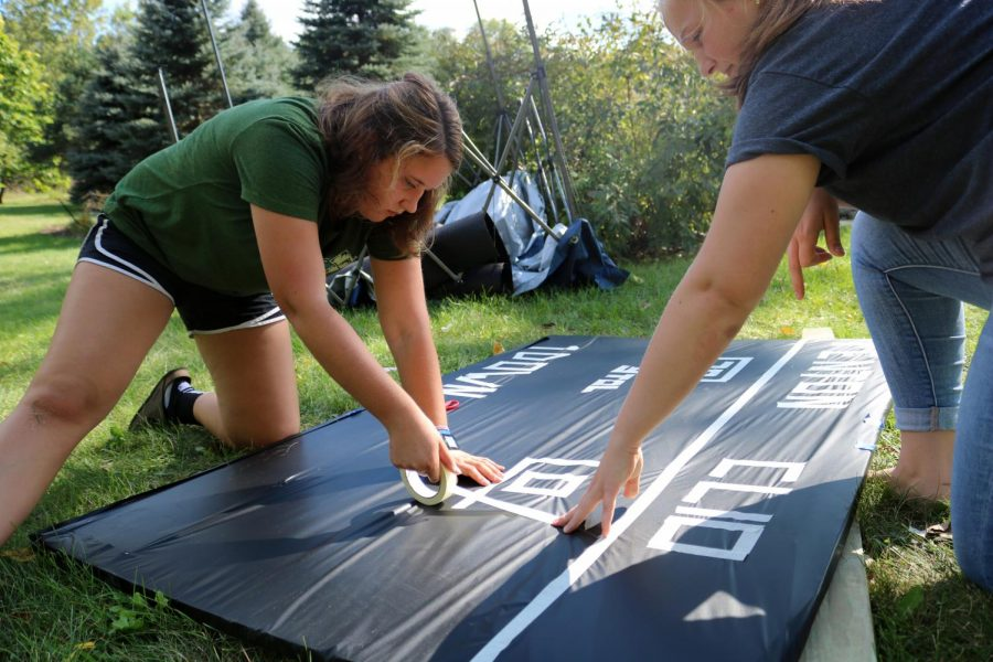 Working diligently, juniors Abigail Lamb and Alexandria Resa, concentrate working on building the junior float. Later, along with the other class floats, it would participate in the Homecoming parade.