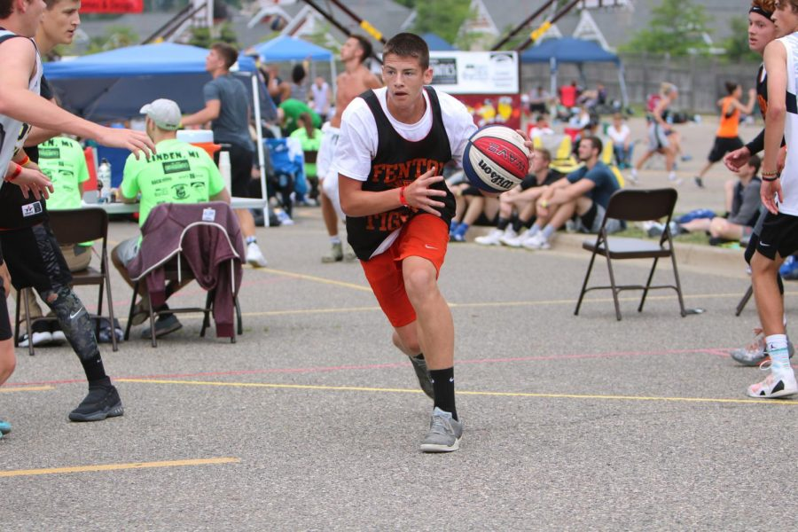 Before passing it to a teammate, Junior Kade Lookebill dribbles a basketball during a tournament on June 28. Fenton High basketball players competed in the Gus Macker Basketball Tournament in Linden.