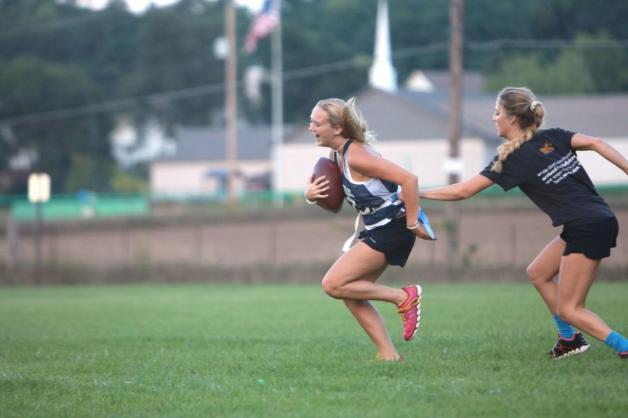 Attempting to avoid an opponent, senior Grace Shepherd runs the football across the field on Sept. 6. Senior girls participated in powder puff practice in preparation for their Homecoming game. The powderpuff game will take place on Monday, Sept. 17 at 7 p.m..