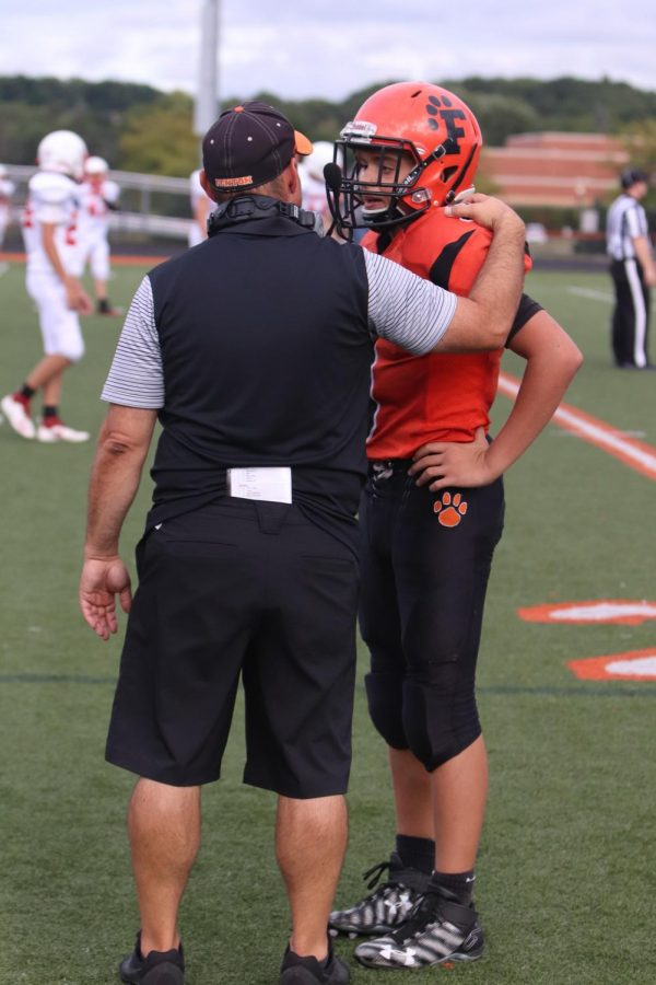 While talking to coach Jeff Adams, freshman Seth Logan is told the next play to run. The freshman football team played against Chippewa Valley at home on Aug. 30.