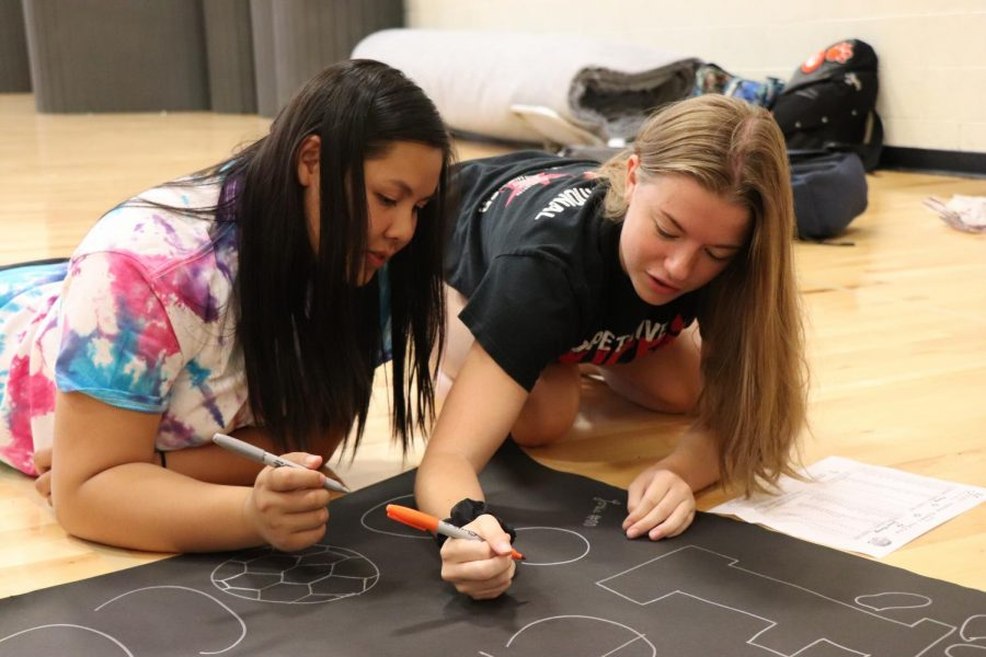 Decorating posters for the fall sports teams, junior Lillian Huynh and senior Maddie Hayden make posters with the rest of the cheerleading team. The cheerleaders also decorate the hallways for the Homecoming game for each grades theme.