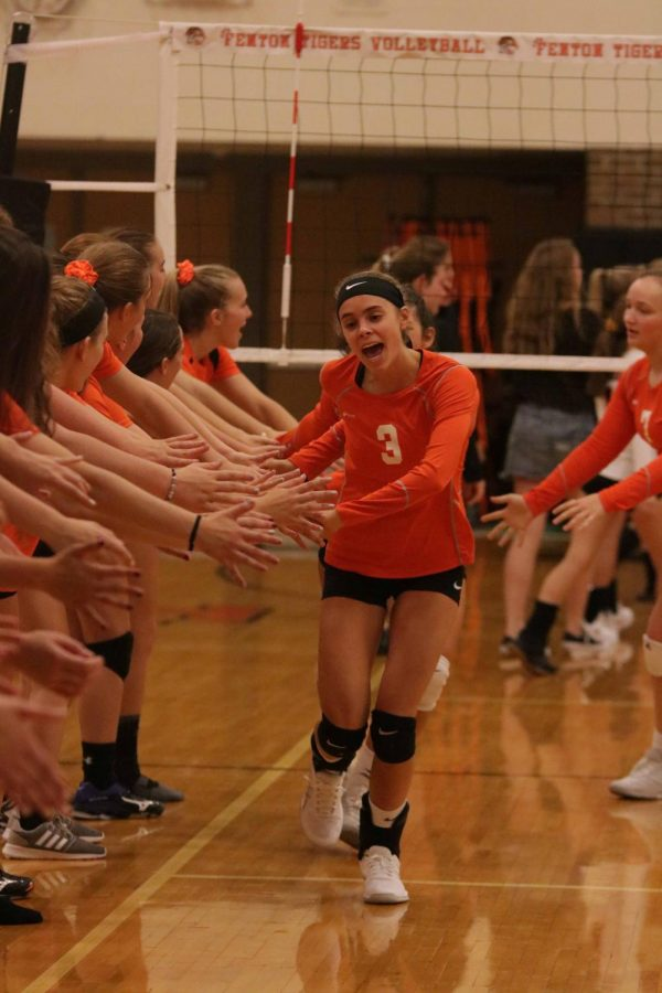 Leading the team, junior Anna Weigle cheers loudly as she runs through the hands of the freshmen and JV teams.  The girls won the game against Clio 3-0.