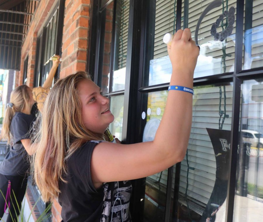 With one marker in her hand, freshman Emily Blunden draws on the Fenton House window. Members of the student council went to downtown Fenton to decorate  stores to celebrate homecoming.