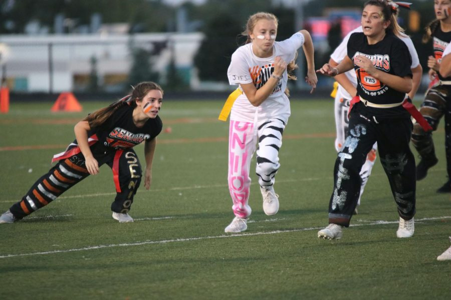 Making a sharp turn, senior Julia Stocker runs after the opposing team on Sept. 17. Senior and junior girls played powder puff to celebrate Homecoming, with the seniors winning the game.