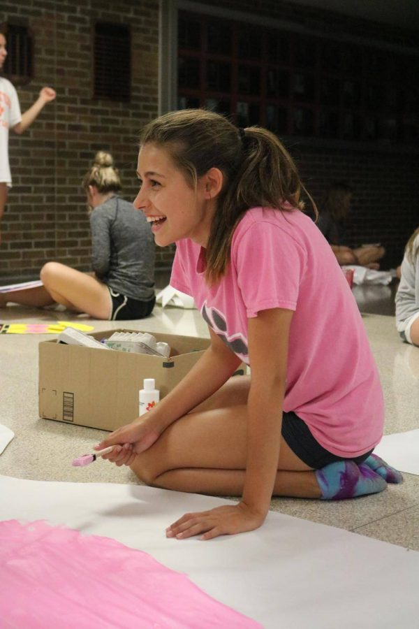 Dipping her paintbrush into the pink paint, freshman Laura Singer draws on the white poster. The cheerleaders decorated the Fenton High hallway on the night before homecoming.