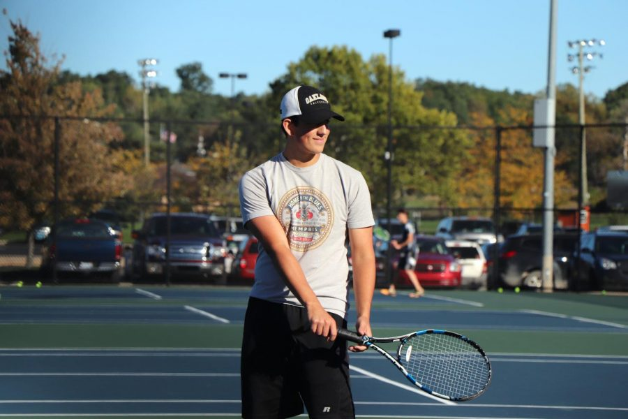 A good serve starts off a tennis match. During practice, senior Ethan Gutzeit helps coach Gary Ballard give pointers on serving techniques. Practice ended well on Oct. 4.