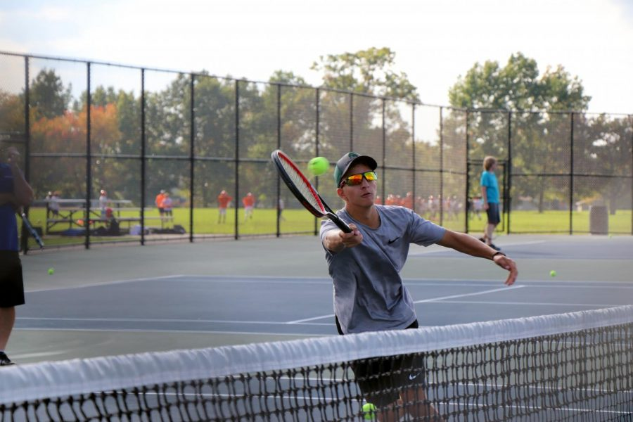 On Oct 9, during the Varsity tennis boys' practice, junior Trevor Bloss serves the ball back to his coach. They wrapped up their season last night.