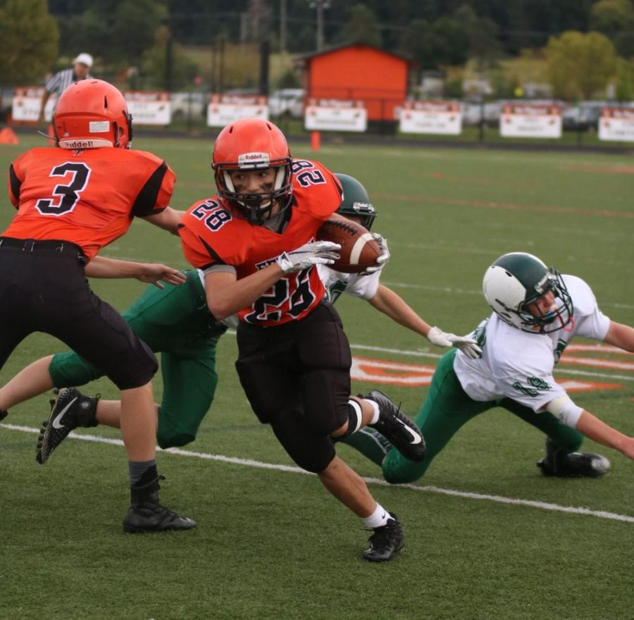 While+he+runs+down+the+field%2C+freshman+Trey+Hale+passes+the+defensive+line.+The+freshman+football+team+played+Alpena+on+Sep.+27.