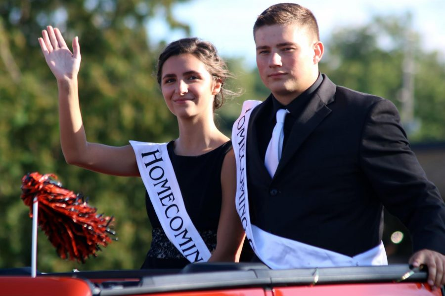While riding down the streets of downtown Fenton, seniors Madi Bluthardt and Lance Mercord wave to the people on the streets.  They later went to the homecoming football game and dance.