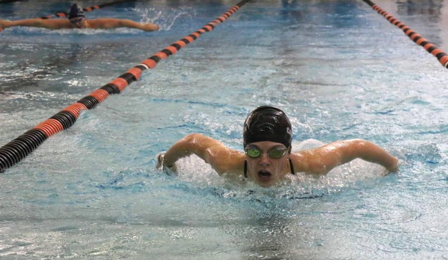 With her Owosso opponent behind her, freshman Abbey Carrigan finishes the 200 yard butterfly. Carrigan beat her opponent and the team came out on top during the meet on Sept. 29.