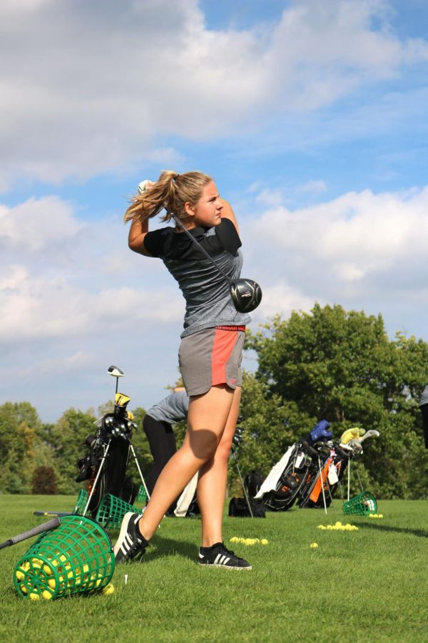 During golf practice, french exchange student Charlotte Cunaud hits a ball on the driving range on Oct. 3. The varsity girls golf team practiced hitting and putting at The Preserve.