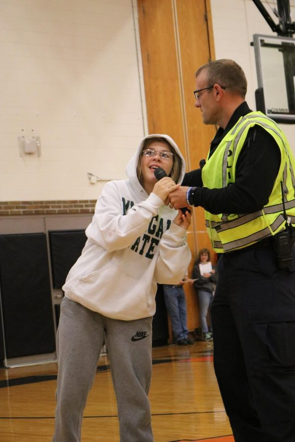 Microphone in hand, junior Meg Wolosonowich reassures the entire school that the gun used in the ALICE training, was indeed fake. Officer Tom Cole led the school wide ALICE training on Oct. 5 for Fenton High.