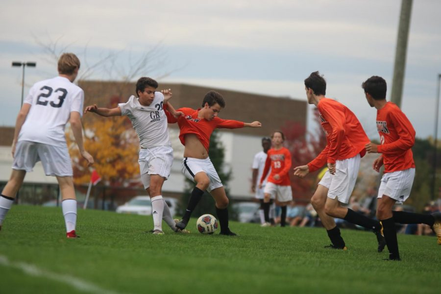 Trying to keep on the ball, sophomore Nick Grigorian dodges a  Grand Blanc Bobcat. The boys JV and varsity soccer teams played against the Bobcats on Oct. 10.