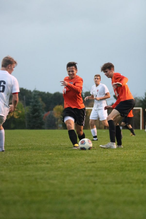 With intense determination, junior Alex Flannery dribbles the ball up the field to attempt to score a goal. The boys varsity soccer team played against Grand Blanc on Oct. 10.