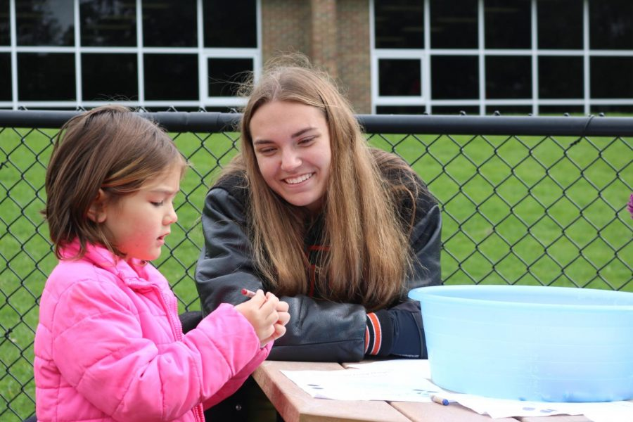 On pond day, junior Jessica Adams observes a Tomek Eastern first grader coloring. Anatomy and physiology and IB Biology students participated in pond day on Oct. 12.
