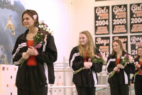With flowers in their hands, the Fenton High girls swim team celebrates senior night on Oct. 25, 2018. The senior girls did their yearly tradition by jumping into the pool after their names are called.