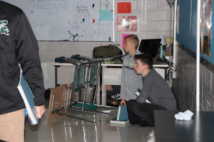 While the school participates in a ALICE training drill, freshman Chase Coleman and Riley Smith are hiding behind two desks and waiting for the shooter to come. This training drill took place on Oct. 5.