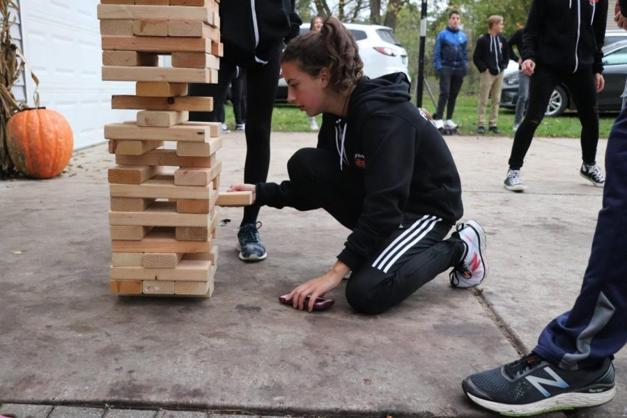 Freshman Ella Cox is in the middle of a game of Jangga with her cross country teammates at the pasta party on Oct. 12. At her race on Saturday she got 10th for Fenton varsity.