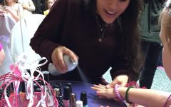 While volunteering at the Princess Ball for World of Wonder, senior Minna Ramirez sprays a finishing polish on one of the girl's nails. On Oct. 13 and 14, NHS members helped run the show for kids attending the ball.