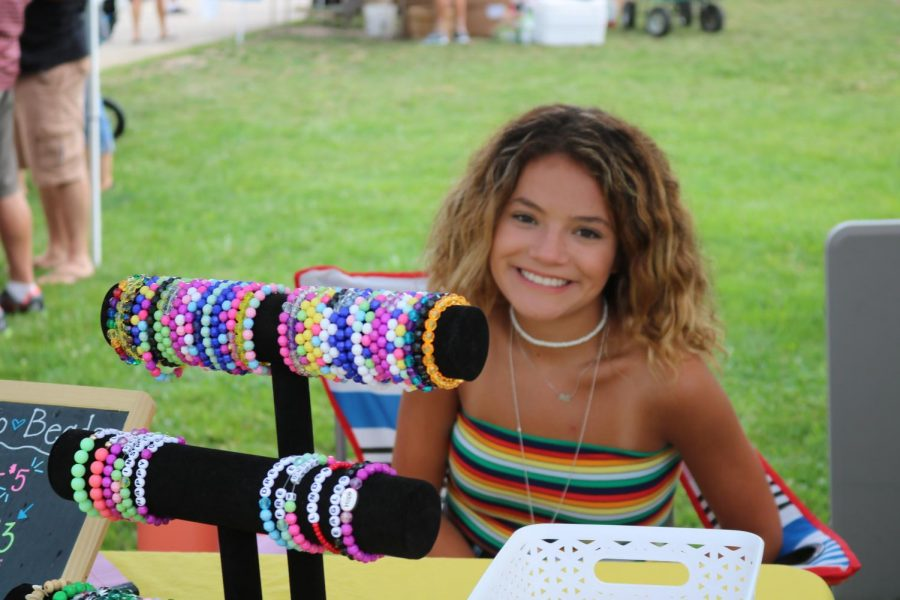 During the farmer's market in downtown Fenton, sophomore Fiona Suydam beaded bracelets to customers.