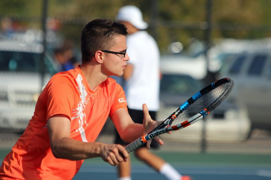 Polish exchange student Tymek Barcinski hits the ball over the net to his opponents.