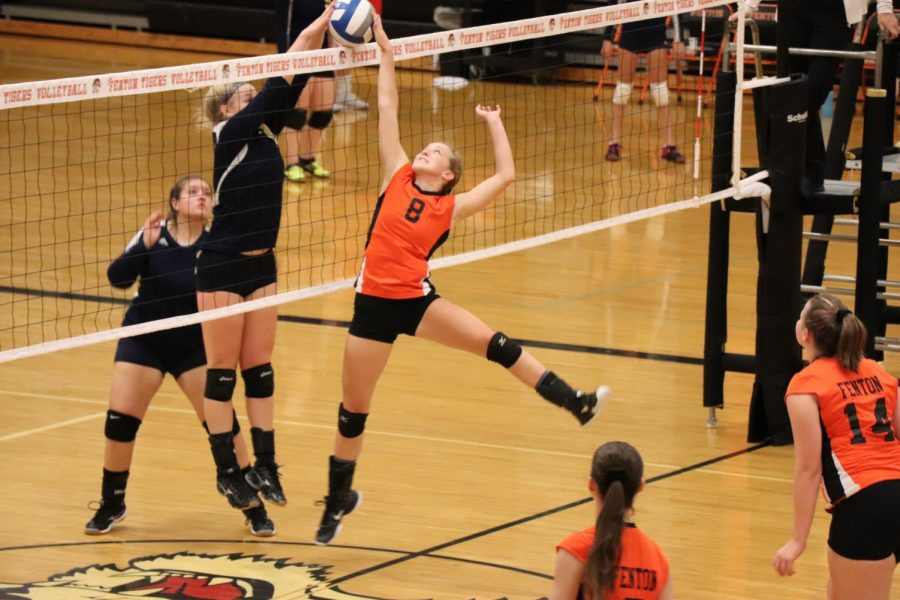 To save the ball from going over, sophomore Mallory Lehmann leaps into the air to block the incoming spike from opposing team Owosso.