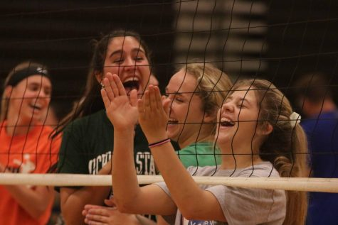 While watching the parents, junior Meg Wolosonovich laughs at the parents as they warm-up for Family Fun Night.  On Oct. 3, the volleyball program and parents played each other in a game of volleyball.