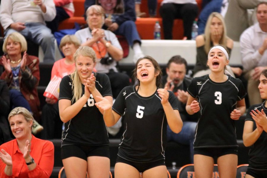 After winning the play, sophomore Sydney Sahr and juniors Jessie Bright and Anna Weigle cheer their teammates on against Goodrich.  Oct. 24 was parent and senior night where the volleyball program honored the parents and seniors.