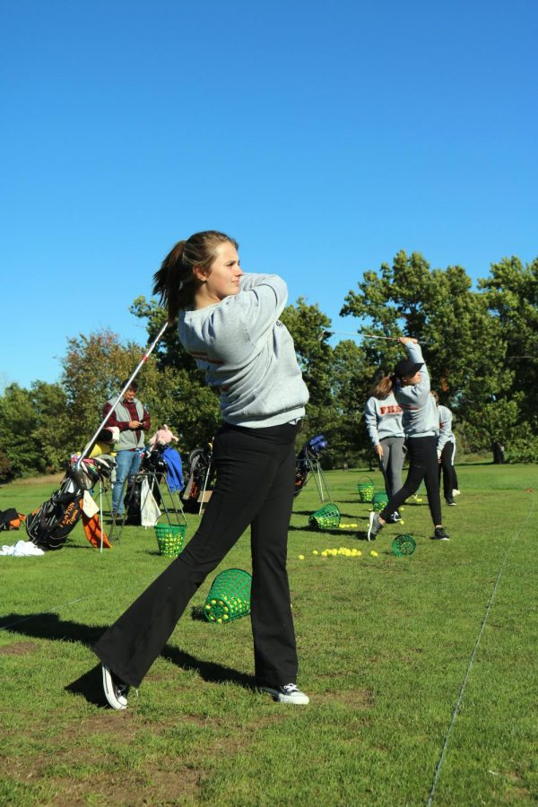During varsity golf practice, senior Ava Stebbins hits a ball on the drive range at The Preserve. The girls golf team had their final practice on Oct. 18, finishing the season.