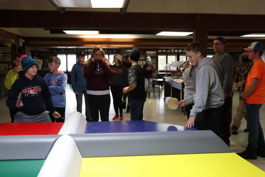 At camp for the fenton Ski Team bonding junior Mitchell Scheer is playing polly pong. Senior Charlotte Cunaud watches and hopes that he does not miss the ping pong ball.