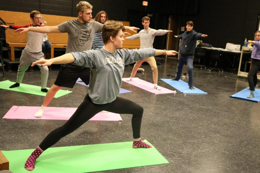 Junior Sheehan Personette focuses on the warrior pose with her fellow IB Theater students.  Librarian Rachael Hassell went to different classrooms to teach yoga as a way of relieving stress.