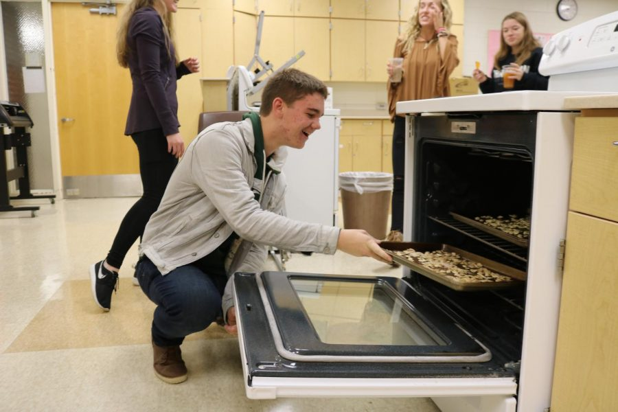 Senior Jack Haynes puts pumpkin seeds in to the oven. The IB french class made cinnamon sugar pumpkin seeds to celebrate Halloween.