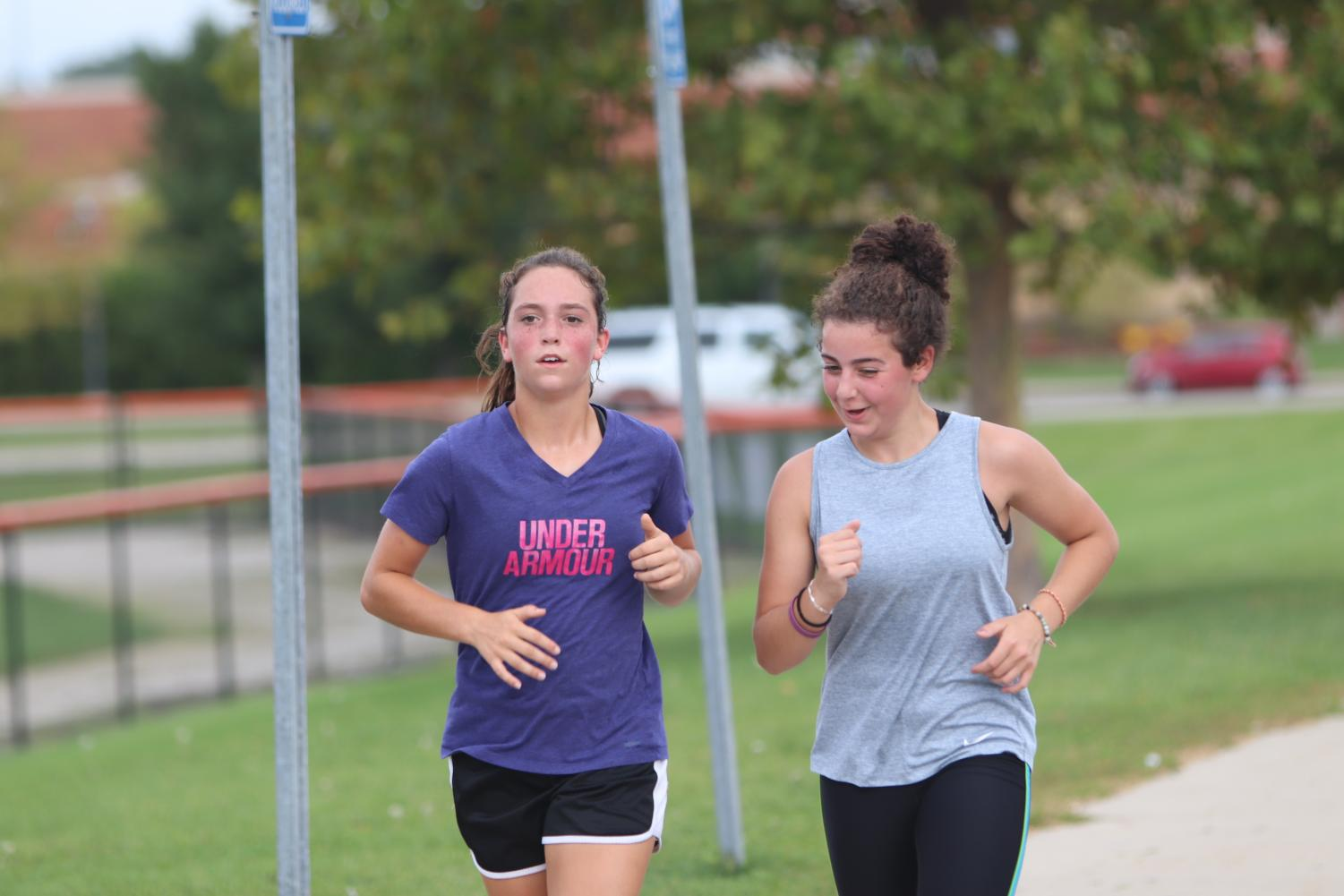 Freshmen Taylor Huntoon (left) and Angelina Vitarelli (right) run together during practice. Both girls are members of the Fenton cross country team