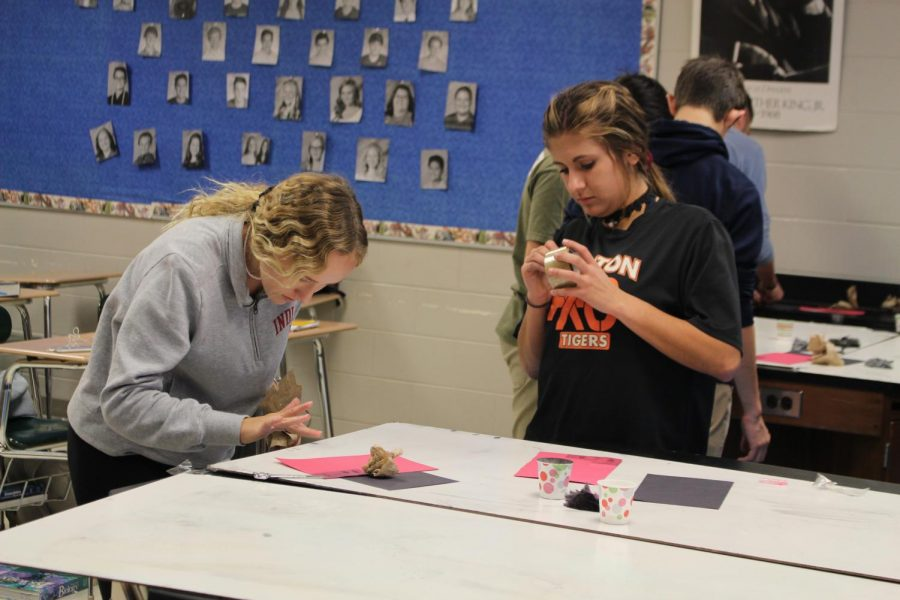 Seniors Cami Tiemann and Abbey Lee dust their fingerprints in a lab. Officer Tom Cole worked with Forensics students on Nov. 13 to learn about checking fingerprints on crime scenes.
