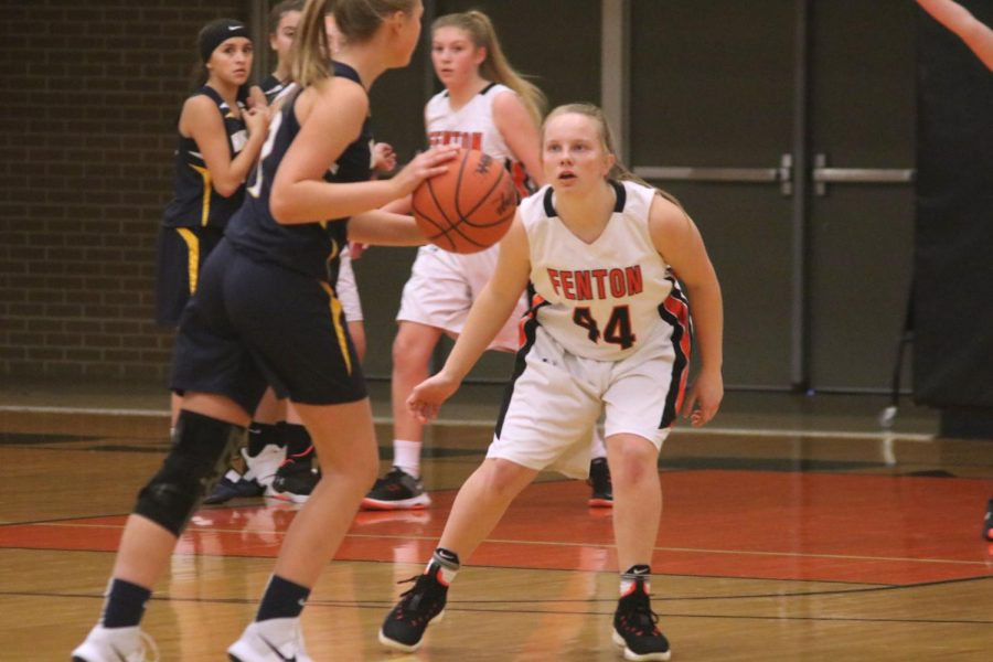 Watching her opponent, freshman Dylyn Nichols prepares to block the ball. On Dec. 4, the freshman girls basketball team played Hartland at home.