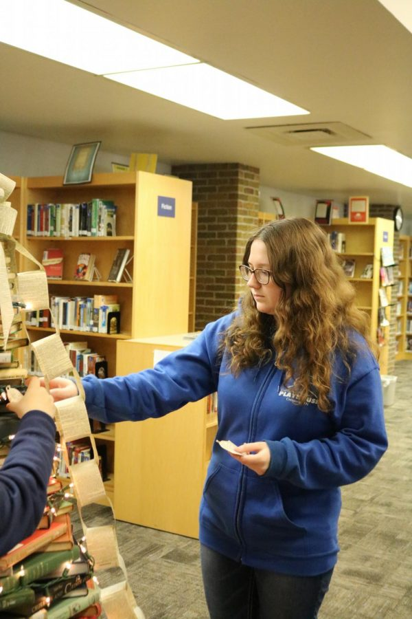 Senior Gracie Niec decorates the Christmas tree in the media center. Media Services students built a tree out of books to decorate the media center for the holiday season.