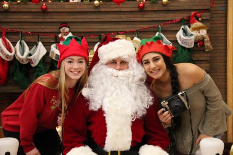 Seniors Lauren Murphy (left) and Zena Alshomali (right) pose for a photo with Santa. Students volunteered on Dec. 1 at the Brunch with Santa for the annual Jinglefest festivities.