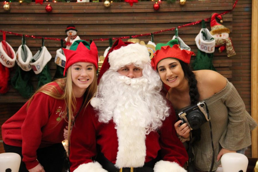 Seniors+Lauren+Murphy+%28left%29+and+Zena+Alshomali+%28right%29+pose+for+a+photo+with+Santa.+Students+volunteered+on+Dec.+1+at+the+Brunch+with+Santa+for+the+annual+Jinglefest+festivities.+