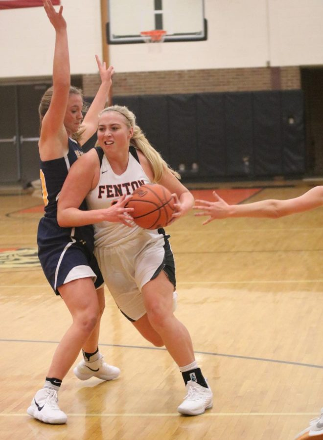 During the second quarter, senior Chloe Idoni pushes past a Hartland defender. The girls varsity basketball played their first home game against Hartland on Dec. 4.