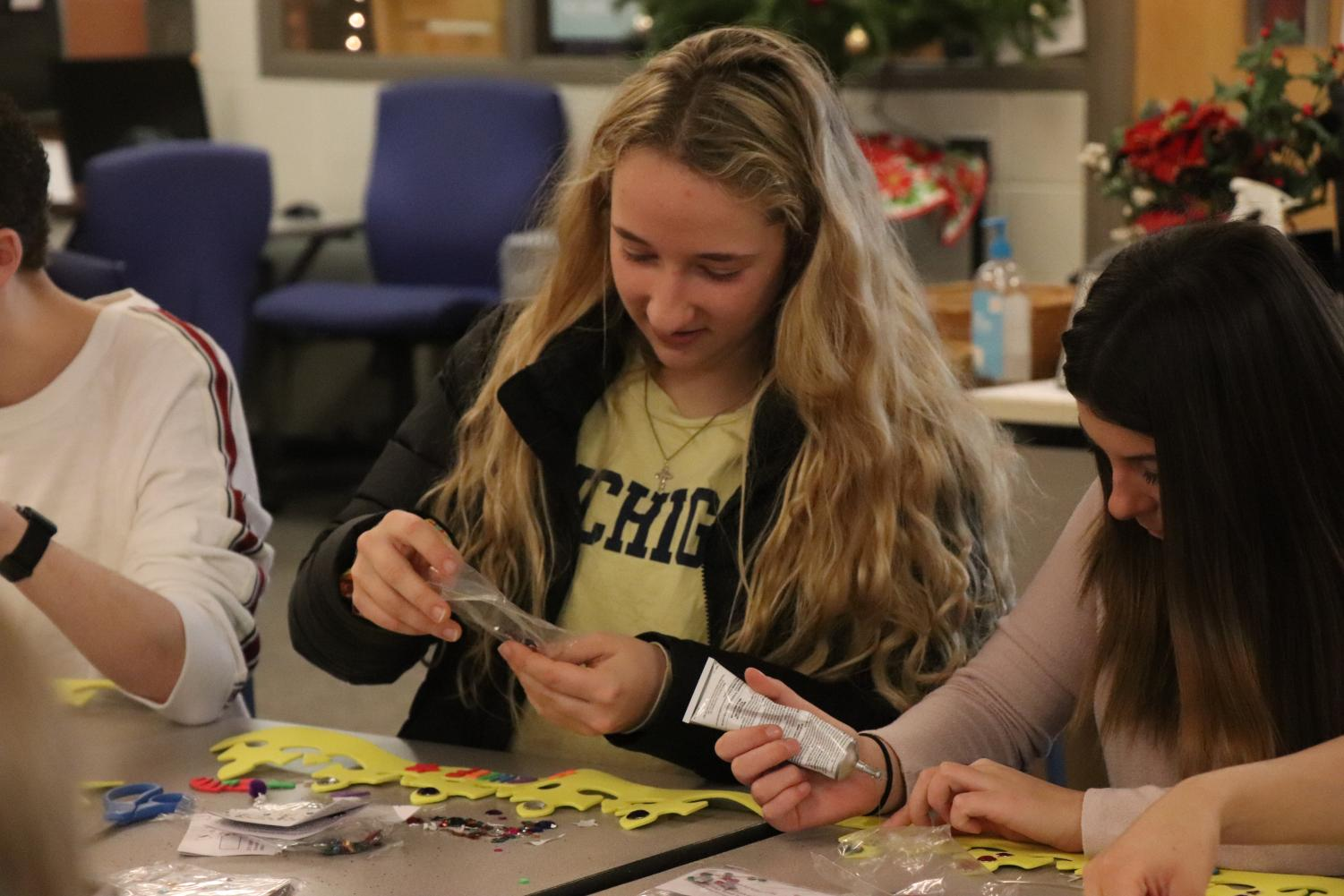 Seniors Lauren Lamb and Rachel Smith decorate crowns with the rest of the yearbook staff. Yearbook staff members decorated crowns on Dec.  3 as a