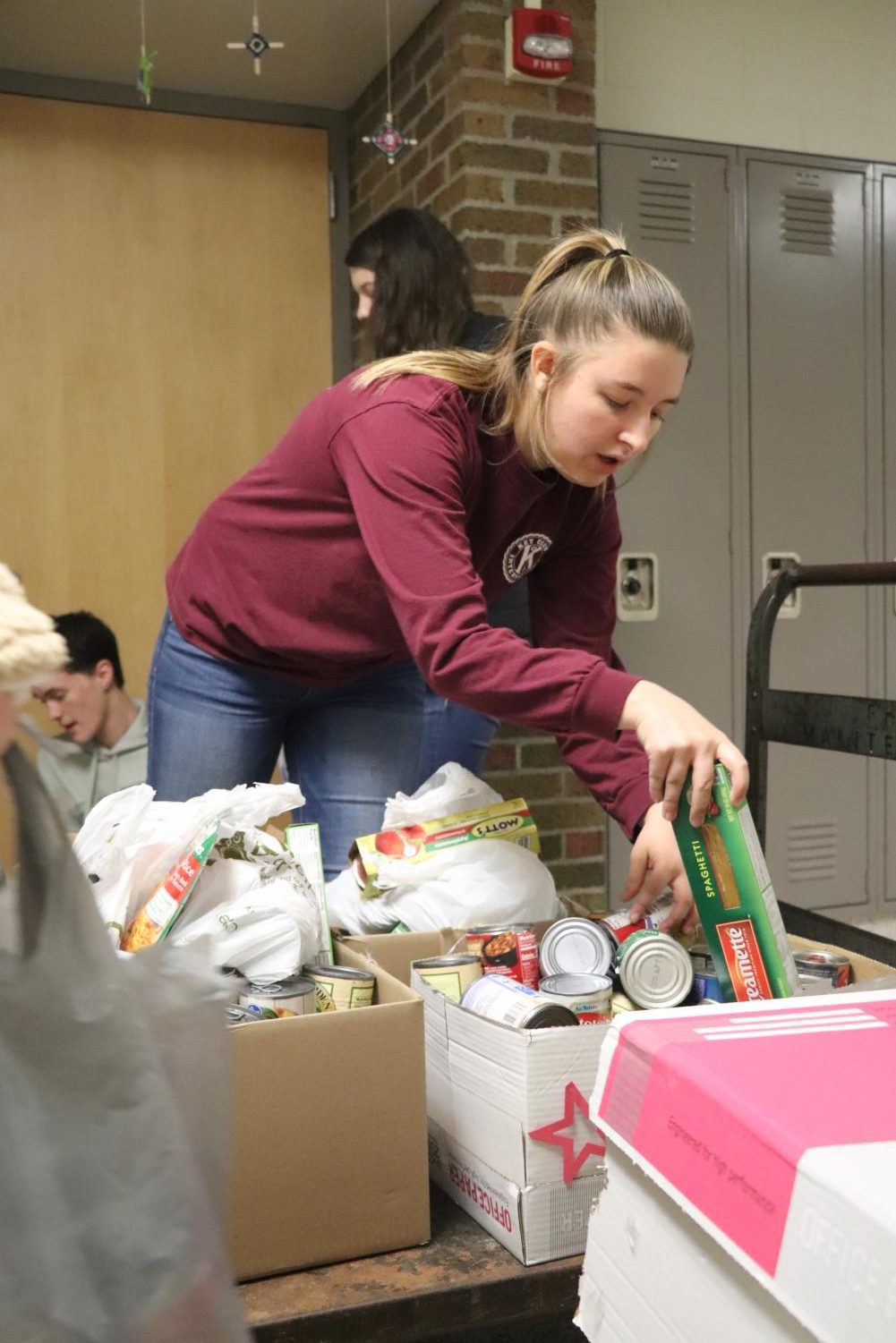 Senior Maci Best puts food on a cart during the Key Club food drive pick-up. On Dec. 17, Key Club members picked up food around the school that students brought in to their SRTs for the food drive.