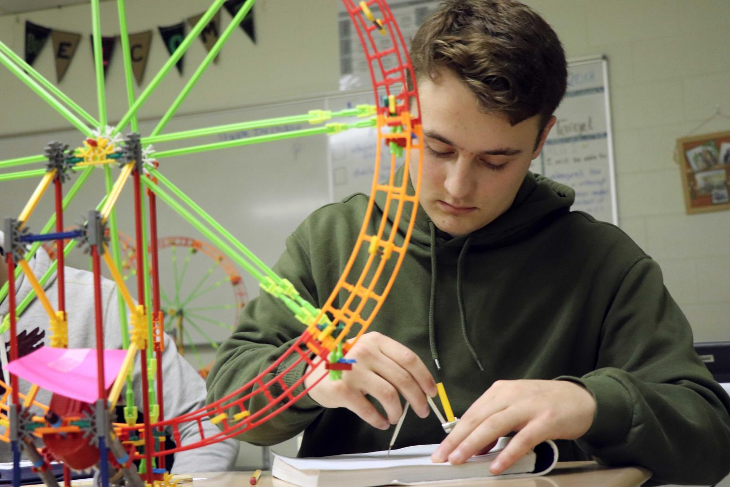 While measuring his ferris wheel, senior Thomas Conlon draws the wheel for his scale drawing.  Students in Algebra 2 (Year 2) built their own ferris wheel and will graph sinusoidal equations for the project.