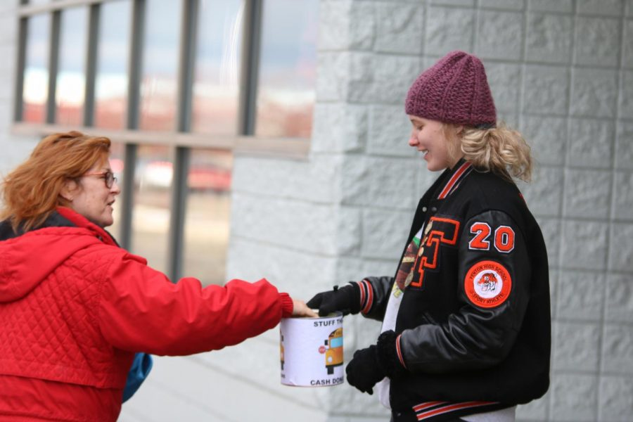 With her hand stretched out, junior Lydia Podlesak accepts money for Stuff the Bus. National Honor Society members help by taking their time to ask for money or food to help Stuff the Bus.